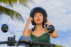 Young pretty happy and cute Asian Chinese woman adjusting motorcycle helmet riding on scooter motorbike isolated on a blue sky in. Safe bike ride safety and Stock Image