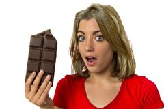 Pretty happy and excited girl holding big chocolate bar in sugar addiction temptation looking guilty skipping diet in unhealthy nu. Young pretty happy and Royalty Free Stock Photos