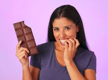 Young pretty and happy hispanic woman holding chocolate bar with teeth bite smiling in sugar and sweet addiction concept Royalty Free Stock Photography