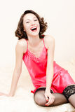 Young pretty happy laughing pinup woman wearing pink dress and stockings Stock Photography