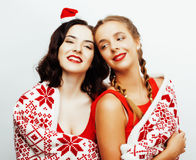 Young pretty happy smiling blond and brunette woman girlfriends on christmas in santas red hat and holiday decorated Royalty Free Stock Photos