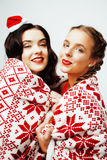 Young pretty happy smiling blond and brunette woman girlfriends on christmas in santas red hat and holiday decorated Stock Images