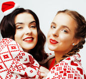 Young pretty happy smiling blond and brunette woman girlfriends on christmas in santas red hat and holiday decorated Royalty Free Stock Images