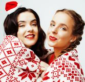 Young pretty happy smiling blond and brunette woman girlfriends on christmas in santas red hat and holiday decorated Royalty Free Stock Photo