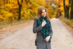 Young pretty happy smiling european woman in an elegant gray coat with a fashionable green warm scarf walks in a golden park. On an autumn afternoon. Cheerful royalty free stock photos