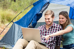 Young pretty hiker couple sitting in a tent looking at laptop Stock Images
