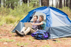 Young pretty hiker couple sitting in a tent looking at laptop Royalty Free Stock Photo