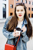 Young pretty hipster girl student with coffee cup posing adorable smiling, lifestyle people concept outdoor Royalty Free Stock Photos