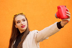 Young pretty hipster girl in yellow sunglasses make selfie by pink instant camera on orange wall. Urban style. Perfect Royalty Free Stock Photography