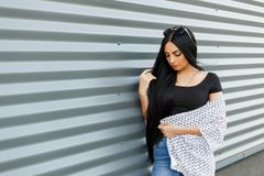 Young pretty hipster woman with long hair in round sunglasses in a black trendy top in a vintage summer jacket in blue jeans royalty free stock images