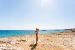 Young pretty hot sexy woman on the tropic island in summer near the sea and blue sky having fun. Stock Photos