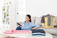 Pretty housewife folding family messy clothing. Young pretty housewife folding family messy clothing in living room and holding tv remote control choosing movie Stock Photo