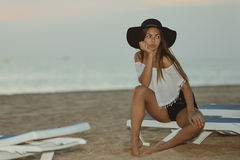 Young pretty lady on beach relaxing in the evening on summer outdoors background, vacation travel Stock Images