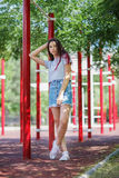 A young pretty lady in casual clothes on a blurred natural background. Fashion, urban, youth concept. Copy space. royalty free stock photography