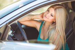 Young pretty lady with a modern luxury car Stock Image