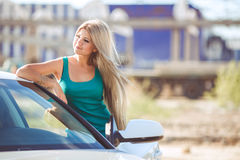 Young pretty lady with a modern luxury car Stock Images