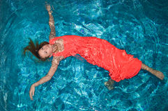 Young pretty lady in red with spread arms and legs. Young pretty lady with spread arms and legs floating on swimming pool in long red dress Stock Images