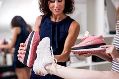 Young pretty lady standing at one leg while her friend checking new footwear size comparing it with old shoes sole royalty free stock photography