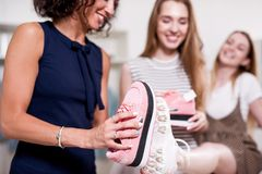 Young pretty lady standing at one leg while her friend checking new footwear size comparing it with old shoes sole royalty free stock photos