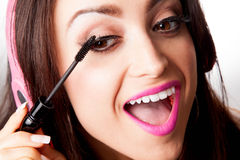 Young Pretty Latino Woman Putting on mascara. While listening to Headphones Stock Image