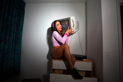 Young Pretty Latino Woman sitting in a hotel room. Lifting a vintage television set above her head Royalty Free Stock Images