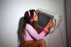 Young Pretty Latino Woman sitting in a hotel room. Lifting a vintage television set above her head Stock Image