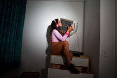 Young Pretty Latino Woman sitting in a hotel room. Lifting a vintage television set above her head Stock Photos