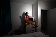 Young Pretty Latino Woman sitting in a hotel room. Lifting a vintage television set above her head Royalty Free Stock Image