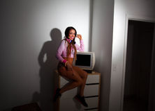 Young Pretty Latino Woman sitting in a hotel room. Lifting a vintage television set above her head Stock Images