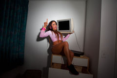 Young Pretty Latino Woman sitting in a hotel room. Lifting a vintage television set above her head Stock Photography