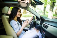 Young pretty looking to her smartphone while driving car on the road royalty free stock images