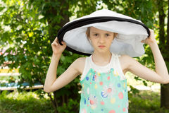 Young Pretty Mad Girl in Round Big White Hat Royalty Free Stock Photography