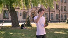 Young pretty male student in white shirt standing and holding phone, park near university background.  stock video