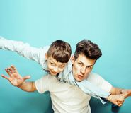Young pretty man model with little cute son playing together, li. Young pretty men model with little cute son playing together, lifestyle modern people concept stock image