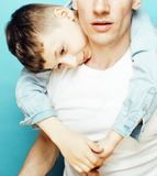 Young pretty man model with little cute son playing together, li. Young pretty men model with little cute son playing together, lifestyle modern people concept Royalty Free Stock Image