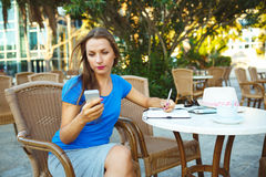 Young pretty modern blogger using smartphone and makes notes in Stock Image