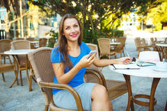 Young pretty modern blogger using smartphone and makes notes in Stock Photo