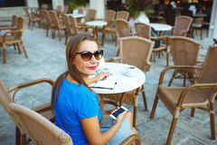 Young pretty modern blogger using smartphone and makes notes in Royalty Free Stock Photo