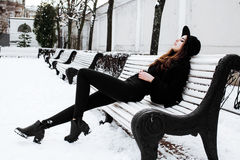 Young pretty modern hipster girl waiting on bench at winter snow park alone, lifestyle people concept Royalty Free Stock Photography