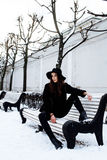 Young pretty modern hipster girl waiting on bench at winter snow park alone, lifestyle people concept Stock Photo