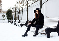 Young pretty modern hipster girl waiting on bench at winter snow park alone, lifestyle people concept Stock Photos