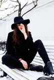 Young pretty modern hipster girl waiting on bench at winter snow park alone, lifestyle people concept Stock Images