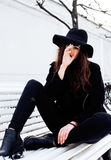 Young pretty modern hipster girl waiting on bench at winter snow park alone, lifestyle people concept Stock Photography