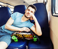 Young pretty modern hipster guy traveller on train with skateboa Royalty Free Stock Photo