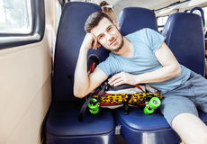 Young pretty modern hipster guy traveller on train with skateboard alone, lifestyle vacation people concept Royalty Free Stock Image