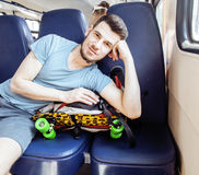 Young pretty modern hipster guy traveller on train with skateboard alone, lifestyle vacation people concept Royalty Free Stock Photography