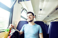 Young pretty modern hipster guy traveller on train with skateboard alone, lifestyle vacation people concept Stock Image