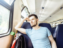 Young pretty modern hipster guy traveller on train with skateboard alone, lifestyle vacation people concept Royalty Free Stock Photos