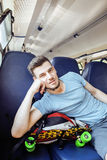 Young pretty modern hipster guy traveller on train with skateboard alone, lifestyle vacation people concept Stock Photo