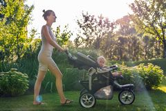 Young pretty mother with baby in stroller enjoying walking in green fresh garden at sunset. Mom having fun with baby in pram in be